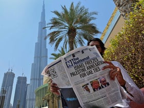 A man reads a copy of UAE-based The National newspaper near the Burj Khalifa, the tallest structure and building in the world since 2009, in the gulf emirate of Dubai, August 14, 2020