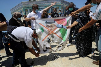 People burn a picture depicting Abu Dhabi Crown Prince Mohammed bin Zayed during a protest against the UAE's normalization deal with Israel, in Jerusalem's Old City, August 14, 2020