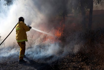 A firefighter tackles a blaze that broke out in southern Israel, August 11, 2020.