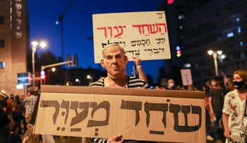 Protesters carry a sign that reads 'bribery blinds' in Jerusalem, August 15, 2020.