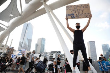 A protesters on a bridge in Tel Aviv carries a sign that reads, 'Thanks for Dubai, yalla bye,' August 15, 2020.