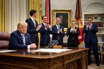 White House officials clap for President Donald Trump after he announced an agreement between the UAE and Israel, in the White House, August 13, 2020.