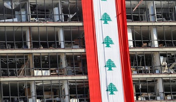 Lebanese flag draped over a damaged building in the aftermath of the massive explosion in Beirut's port, Lebanon, August 15, 2020.
