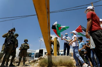 Demonstrators hold Palestinian flags in front of Israeli soldiers during a protest against the UAE' deal with Israel to normalize relations, in Haris near Salfit in the West Bank, August 14, 2020.