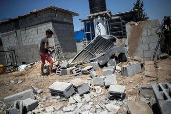A Palestinian boy inspects the damage in his family home following Israeli airstrikes in Buriej refugee camp, central Gaza Strip, August 15, 2020.