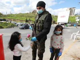 Palestinian children with a Palestinian security forces member