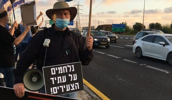 """Bentzion Arad, 80, from Sde Warburg. One sign reads: """"I fought four wars for this country. This one is my fifth!"""" The other states: """"We're fighting for the future of our youth!"""""""