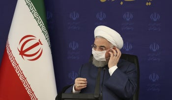Iranian President Hassan Rohani adjusts his face mask in a meeting of the national headquarters of the fight against the COVID-19, Tehran, July 18, 2020