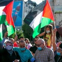 Palestinian protesters lift national flags during a demonstration against the Emirati-Israeli agreement, Ramallah, August 15, 2020.