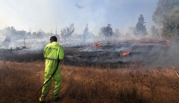 A firefighter extinguishing a fire near Kibbutz Be'eri Kibbutz, caused by an incendiary balloon launched from the southern Gaza Strip, on August 16, 2020.
