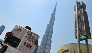 """A man reads a copy of UAE-based The National newspaper near the Burj Khalifa, the tallest structure and building in the world since 2009, in the gulf emirate of Dubai on August 14, 2020, as the publication's headline reflects the previous day's news as Israel and the UAE agreed to normalise relations in a landmark US-brokered deal. - The deal marks only the third such accord the Jewish state has struck with an Arab nation, an historic shift making the Gulf state only the third Arab country to establish full diplomatic ties with the Jewish state. The Palestinian leadership voiced its """"strong rejection and condemnation"""" of the deal and announced it would withdraw its envoy from the UAE, and Turkey also condemned the deal as an act of treachery."""