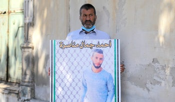 Jamal  Manasra and a poster with a picture of his son Ahmad, in Jaffa, August 17, 2020