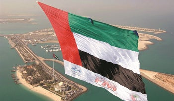 The national flag of the United Arab Emirates is flown over Abu Dhabi December 2, 2007