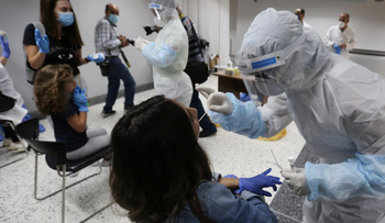 Health workers take swab samples from passengers who arrived at Beirut international airport on its re-opening day following the coronavirus outbreak, in Beirut, Lebanon, July 1, 2020.