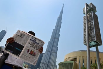 A man reads a copy of UAE-based The National newspaper near the Burj Khalifa in Dubai on August 14, 2020, as the publication's headline reflects the news on the Israel-UAE agreement.