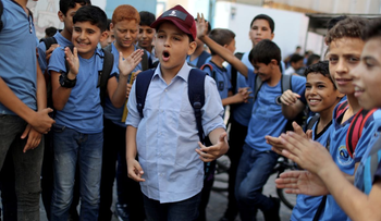 Abdel-Rahman Al-Shantti, an 11-year-old Gaza rapper, is surrounded by students as he performs in his school in Gaza City August 16, 2020.