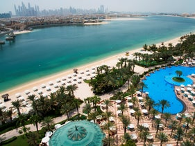 The pool and beach of the Atlantis Hotel is seen with the skyline of the Dubai Marina visible in the distance in Dubai, United Arab Emirates, Tuesday, July 14, 2020.