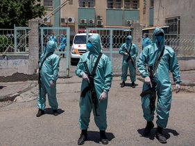 Palestinian Hamas police officers wear protective suits as they take part in a simulation of possible coronavirus infections in Gaza City, July 2020.