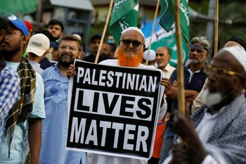 A man holds a sign in support of Palestinian people to condemn the diplomatic agreement between the UAE and Israel, during a protest in Karachi, Pakistan August 16, 2020.