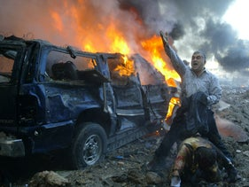 File photo: A Lebanese man shouts for help for a wounded man near the site of a car bomb explosion in Beirut that killed Hariri, February 14, 2005.