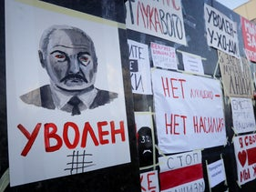 People put anti-Belarusian President Alexander Lukashenko posters on a wall in front of the government building during opposition rally in Minsk, Belarus, August 16, 2020.