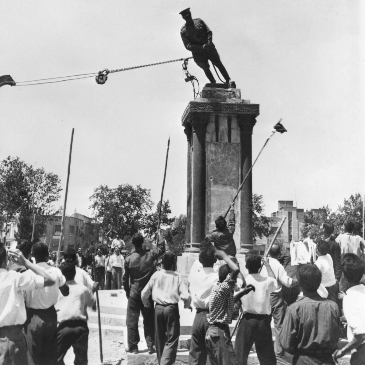 Supporters of then-Prime Minister Mohammad Mossadegh, armed with long sticks, tearing down a statue of the Shah of Iran's father, in Tehran, August 17, 1953. Two days later, Mossadegh was overthrown.