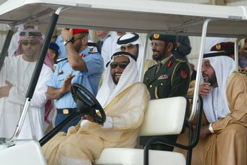 Then UAE President Zayed bin Sultan al-Nahyan (C) and current president Khalifa bin Zayed al-Nayhan (R) attend a military show at the International Defense Exhibition in Abu Dhabi, March 17, 2003.
