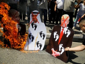 Palestinians burn cutouts depicting U.S. President Donald Trump and Abu Dhabi Crown Prince Mohammed bin Zayed al-Nahyan and Israeli Prime Minister Benjamin Netanyahu during a protest in Nablus against the United Arab Emirates' deal with Israel to normalize relations, on August 14, 2020.