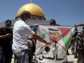 Palestinian protesters in Jerusalem burn a banner showing Abu Dhabi Crown Prince Mohamed bin Zayed al-Nahyan, protesting the UAE's deal with Israel, Aug. 14, 2020. The Dome of the Rock is seen in the backround and the protesters are wearing anti-coronavirus masks.
