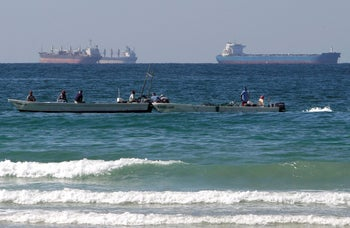 Fishing boats in front of oil tankers on the Persian Gulf waters, south of the Strait of Hormuz, offshore the town of Ras Al Khaimah in United Arab Emirates, January 19, 2012.