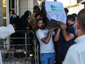 Mourners carry the flag-draped coffin of Reham Yacoub during her funeral procession in Basra, Iraq, Thursday, August 20, 2020.