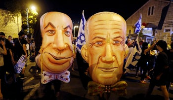 Demonstrators wear masks depicting Netanyahu and Gantz during a protest near the prime minister's residence in Jerusalem, August 8, 2020.