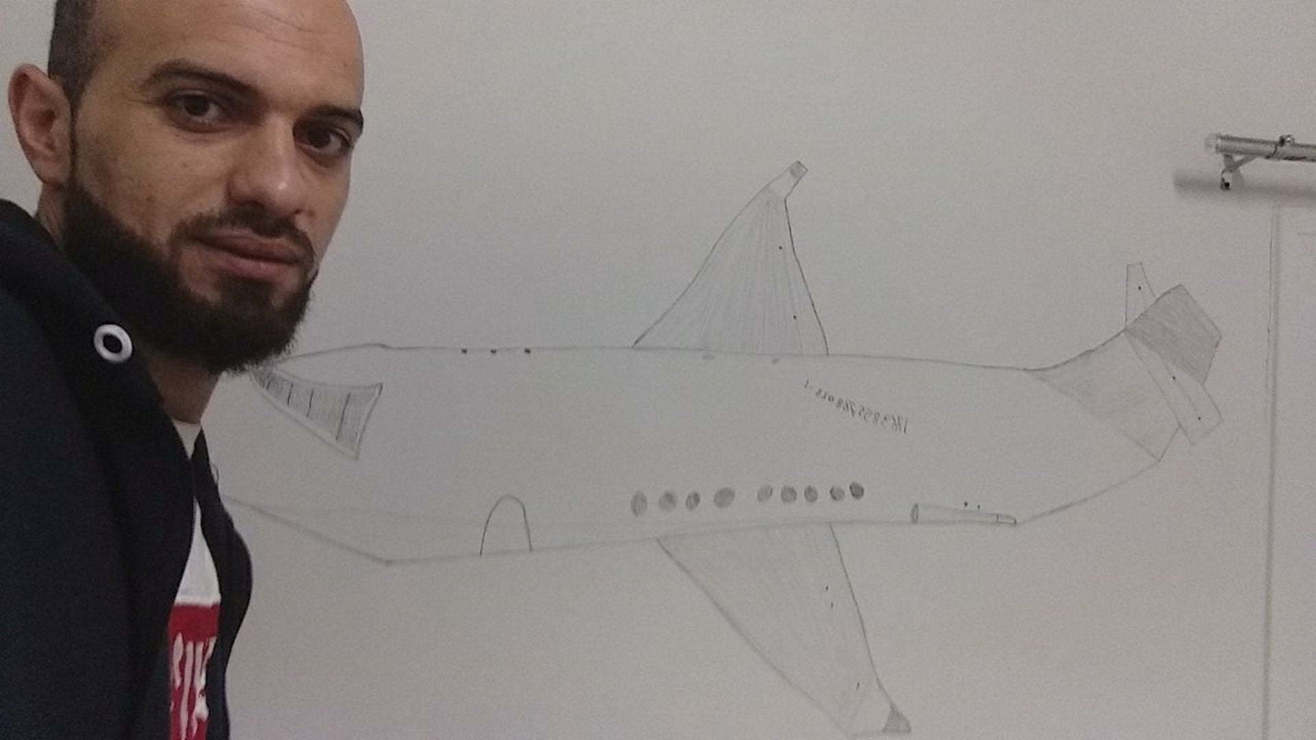 Alaa Alghamri and the plane he drew on the wall of his room.