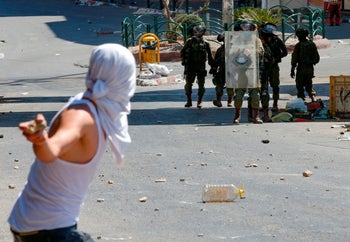 A Palestinian hurls rocks toward Israeli soldiers during clashes following Friday prayers in the city center of the West Bank city of Hebron, on August 14, 2020.