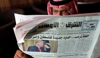 A man holds the daily Asharq Al-Awsat newspaper fronted by a picture of President Donald Trump, at a coffee shop in Jiddah, Saudi Arabia.