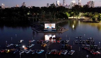"An aerial view shows Israelis watching the movie ""Paddington"" while sitting in distant pedal boats due to the COVID-19 pandemic at the Sail-in floating cinema in Tel Aviv's Hayarkon Park, on August 20, 2020"
