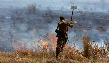 A soldier puts out a fire caused by a balloon launched from Gaza, in southern Israel, August 19, 2020.