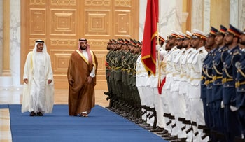 Saudi Crown Prince Mohammed bin Salman, right, inspects an honor guard with Abu Dhabi Crown Prince Mohammed bin Zayed in Abu Dhabi, November 27, 2019.