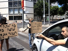 Protesters stand in a road in Tel Aviv, August 23, 2020.