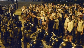 People argue with police during a rally after the Belarusian presidential election in Minsk, Belarus, August 9, 2020.