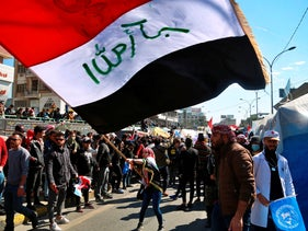 A woman waves an Iraqi flag during a protest in Tahrir Square, Baghdad.