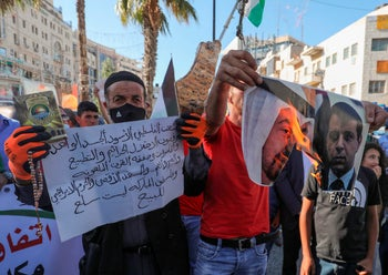 Palestinians burn pictures of Crown Prince Mohammed bin Zayed (L) and Mohammed Dahlan at a demonstration against the Israel-UAE peace deal in Ramallah, August 15, 2020.