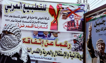 An armed Fatah movement member stands by banners denouncing the US-brokered UAE-Israel deal to normalise relations at a rally at the Askar refugee camp near Nablus. August 22, 2020