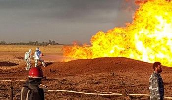 A handout picture released by the official Syrian Arab News Agency early on August 24, 2020, shows firefighters putting out a burning pipeline in the Damascus area.
