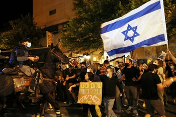 Protesters one waving an Israeli flag, during the anti-Netanyahu demonstration in Jerusalem, August 22, 2020.