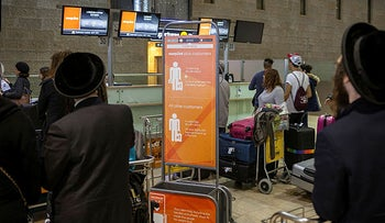 Ultra-Orthodox men stand in front of the EasyJet check-in counter, 2017.