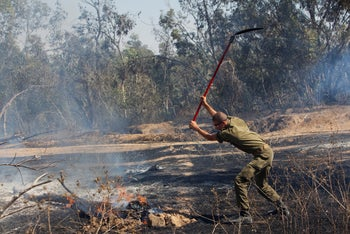 An Israeli soldier putting out a fire at the Kissufim forest