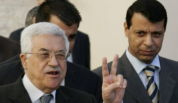 Palestinian Authority President Mahmoud Abbas, left, flashes the V-sign as then Fatah leader, Mohammed Dahlan, looks on in the West Bank town of Ramallah, December 18, 2006