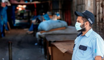 Hamas policeman wearing a protective mask patrols the closed-down Fras local market in Gaza City, August 25, 2020.