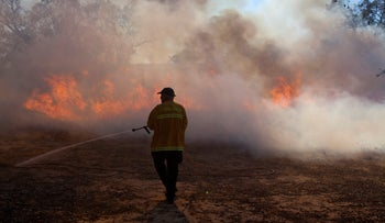 A firefighter works to put out a blaze in southern Israel on August 24, 2020.